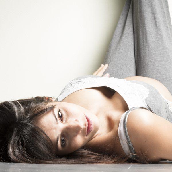 seance-photo-grossesse-future-maman-mom-to-be-ventre-arrondi-hiboux-portrait-sourire-sebastien-huruguen-photographe-gujan-mestras-brune-regard-studio-jambes-contre-le-mur