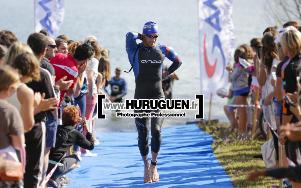 Triathlète sortant de l'eau en combinaison de triathlon sur le triathlon millésime de Cadarsac organisé par le club SAM de Merignac lunette de natation lac de cadarsac bonnet de bain combinaison triathlon ORCA public sortie d'eau soleil