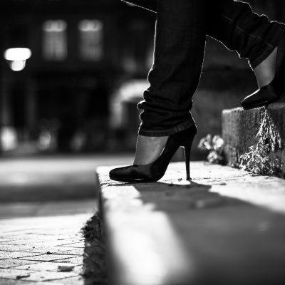 jeune femme portant une paire de jolis escarpins noirs à haut talons gros plan sur les pieds sur les marches d'un escalier rue pavé attente noir et blanc bordeaux mode fashion sebastien huruguen
