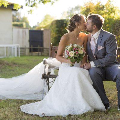 superpe-photo-de-couple-de-jeunes-maries-sur-un-banc-chateau-bordelais-embrassent-bouquet-de-fleurs-robe-a-traine-lumiere-canon-eos-5d-mark-iii-sebastien-huruguen-photographe-mariage-bordeaux