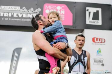 Papa qui termine sa course avec sa fille dans les bras sur la ligne d'arrivée du Scott Half Triathlon - Lacanau Tri Events 2016 | Sébastien Huruguen www.huruguen.fr