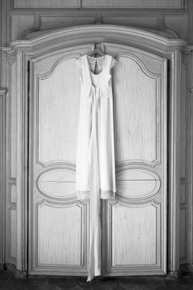 mariage, bordeaux, aquitaine, gironde, sebastien huruguen, photographe mariage, photographe mariage bordeaux, robe de mariage, robe de mariée, robe blanche, porte en bois, vieille porte, belle photo de robe de mariée en noir et blanc suspendue sur un cintre accroché en haut de la porte d'un beau chateau