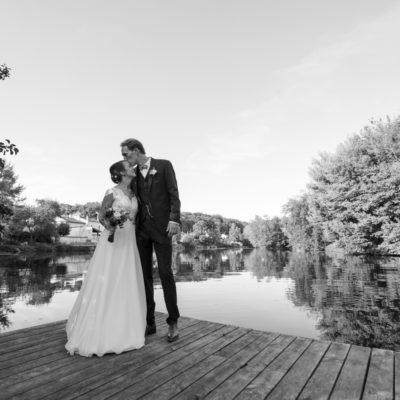 Couple de jeunes mariés s'embrassant sur un ponton du jardin de l'hotel Quai des Pontis au bord de la charente à Cognac sous l'oeil du photographe de mariage bordelais Sébastien Huruguen